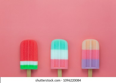 Table top view aerial image of food for summer holiday background concept.Flat lay variety ice cream pop stick on modern rustic pink paper wallpaper.Space for creative design for add text and content.
