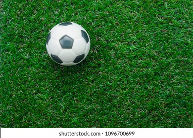 Table top view aerial image soccer or football season background.Flat lay object ball on the artificial green grass wallpaper.Free space for creative design mock up text and wording or content.