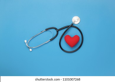 Table top view aerial image of accessories healthcare & medical background concept.Red heart & stethoscope on blue paper.Flat lay essential items for doctor using treat & care patient in hospital.