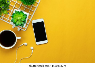 Table top view aerial image of accessories office desk background concept.Flat lay of variety object the white mobile phone & tree pot and coffee with earphone on modern rustic yellow paper and space.