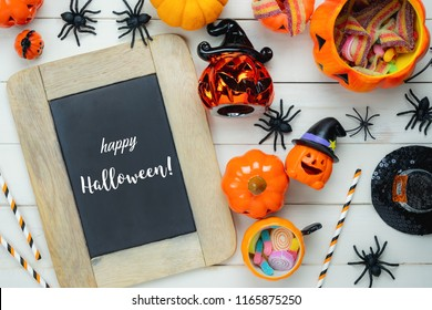 Table top view aerial image of decoration Happy Halloween day background concept.Flat lay accessories essential object to party the pumpkin & candy dessert on white wooden.Text of season on blackboard