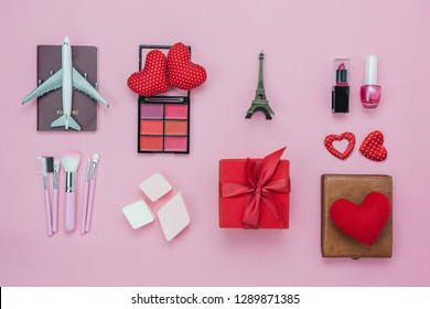 Table top view aerial image of decoration valentine's day background concept.Flat lay essential items red heart & gift box on modern pink paper with clothing women & cosmetic for travel Paris France.