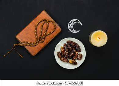 Table top view aerial image of decoration Ramadan Kareem holiday background.Flat lay date with rosary & lighting.Essential object holy Koran of Muslim on modern rustic black wooden at office desk.