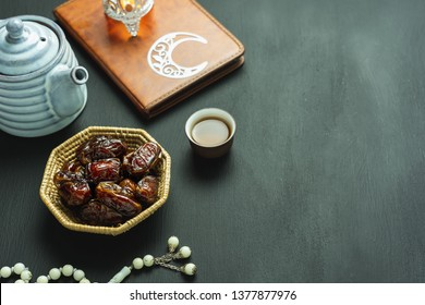Table top view aerial image of decoration Ramadan Kareem holiday background.Flat lay date with rosary & lighting and cup of tea.Essential objects the holy koran on modern rustic black wooden.