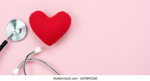 Tafelübersicht Luftaufnahmen von Accessoires Gesundheitswesen & Medizin mit Valentinstag Hintergrund Konzept.Teleskop mit bunten Herzform auf rosafarbenem Papier.Flaches Laienmaterial für Ärzte, die Patienten behandeln.