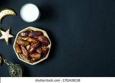 Tafelübersicht Luftbild der Dekorationen Ramadan Kareem Feiertagshintergrund.Flaches Lagedatum mit Rosenkranz und Beleuchtung und Tasse Tee.Halbe Mahlzeiten zum Fasten ist für Muslime auf schwarzem Holz obligatorisch.