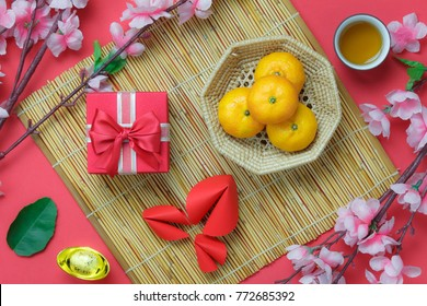 Table top view aerial image of Chinese & Lunar new year background concept.Beautiful gift box & orange with decoration festive.Mix object on the modern rustic red wallpaper at home office desk studio.