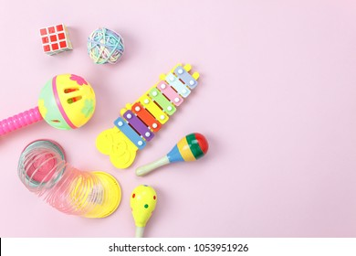 Table top view aerial photo of kids toys collection background concept.Flat lay objects for development children on modern pink paper on office desk.Free space for creative design add text & word.