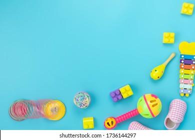 Tischdekoration Kinderspielzeug für die Entwicklung des Grundkonzepts.Flachlegehandschuhe Baby zu spielen mit Gegenständen Kind auf dem modernen blauen Papier am Schreibtisch.Copy Platz für Text.pastellfarbene Tapete.