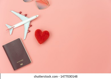 Table top view essential accessory women plan to travel in holiday background.Flat lay of red heart & airplane with passport and love sun glasses on modern pink paper.Love tourism concept.Copy space.