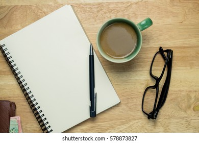 Table top view with glasses, Wallet, coffee cups and book on old rustic wooden background. Concept.