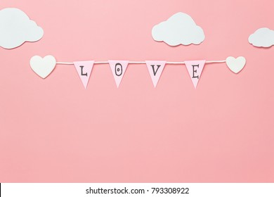 Table top view image of decoration valentine's day background concept.Text sign of season with paper cut clothesline love on beautiful pink sky with cloud.Several objects on pink wallpaper.pastel tone