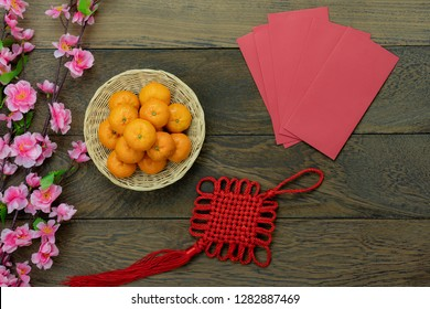 Table top view Lunar New Year & Chinese New Year vacation concept background.Flat lay orange in wood basket & pink cherry blossom with red pocket money & decorations on modern rustic brown backdrop
