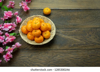Table top view Lunar New Year & Chinese New Year vacation concept background.Flat lay orange in wood basket & pink cherry blossom on modern rustic brown backdrop.free space for creative design.