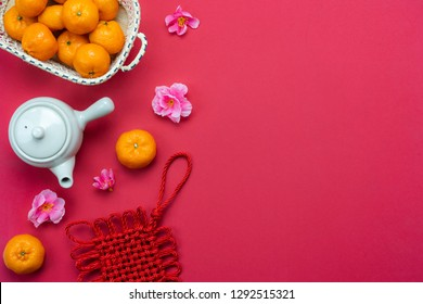 Table top view Lunar New Year & Chinese New Year concept background.Flat lay fresh orange & cup of tea with pink cherry flower and fortune decoration on modern red paper.Copy space for mock up text.