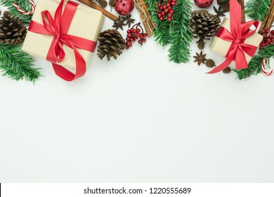 Table top view of Merry Christmas decorations & Happy new year ornaments concept.Flat lay essential objects the fir tree & gift box on modern rustic wood white background at home studio office desk.