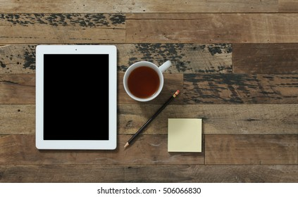 Table top view of office supplies with tea cup against wooden background