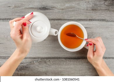 Table top view on young woman hands holding white ceramic teapot in one and silver spoon above cup of hot tea in other.