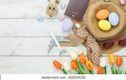 Table top view shot of decoration Happy Easter holiday background with accessory woman to travel concept.Flat lay bunny egg with tulip flower and rabbit doll on modern white wooden at office desk.