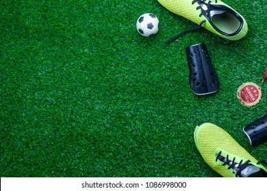 Table top view of soccer or football season background.Flat lay accessories ball with shoe and medal on the artificial green grass wallpaper.Free space for creative design mock up text and content.