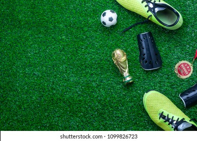 Table top view of soccer or football tournament season background.Flat lay accessories trophy & ball with shoe on the artificial green grass wallpaper.Free space for creative design text and content.