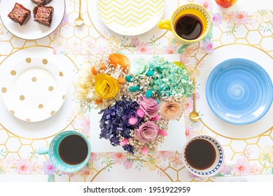 Table top view with sweet snack and coffee with fresh flower centerpiece