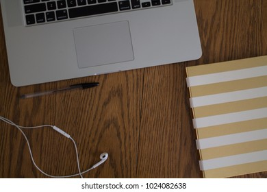table top view of workspace with laptop and ear buds