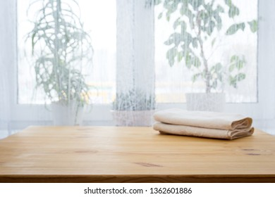 Table with a towel and indoor flowers against the window