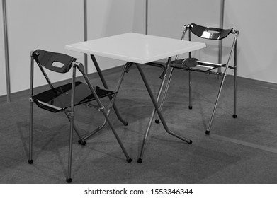 A table and two chairs in the corner of the room. Black and white shot. Side view.