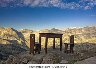 A table and two chairs on an alpine panorama in the light of dawn, outside a mountain refuge.