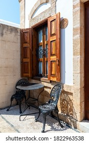 Table and two chairs  under vintage window. Rhodes island, Greece