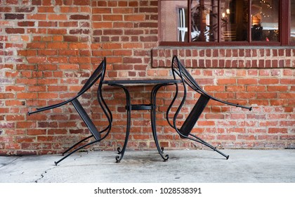 A table for two at a closed  urban outdoor cafe with the iron chairs leaning against the table.
