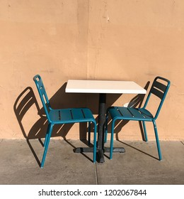 Table and two turquoise chairs outside