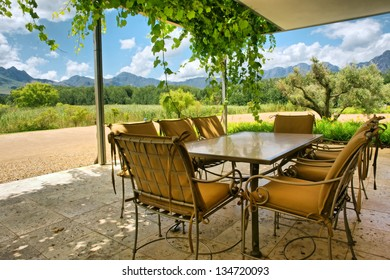 Table in vine-covered pavillion next to magnificent mountains. Shot near Stellenbosch and Cape Town, South Africa.