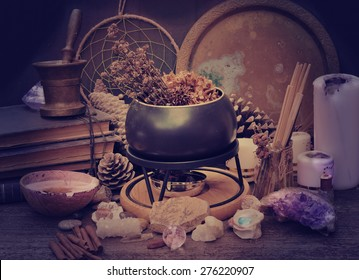 Table warlock with the pot, candles, stones, old books. Vintage style toned photo.
