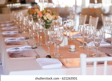 Table at wedding reception decorated with flowers, candles and set with cutlery and crockery