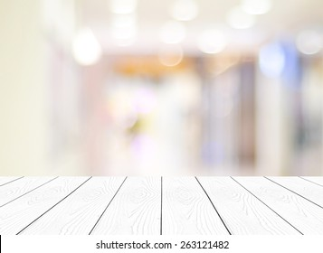Table white wood perspective background, Top of wooden surface, tabletop, and blurred store with bokeh light, Blank  counter, shelf at shop for product display mockup, template, business background