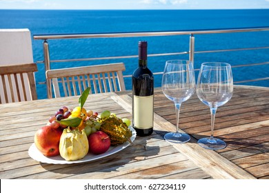Table with wine and fruits next to sea