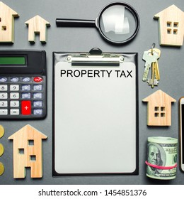 Table with wooden houses, calculator, coins, magnifying glass with the word Property Tax. Property taxes. Calculation of interest on housing tax. Penalty, arrears. Register of taxpayers for property.
