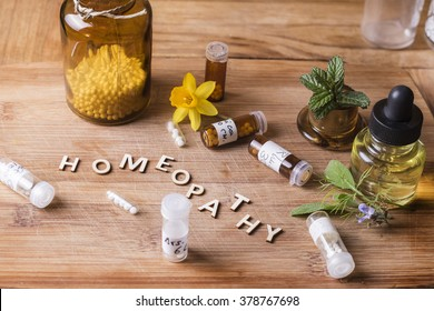 Table with written text Homeopathy, homeopathy globules and bottles