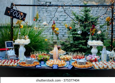 Table in the yard full of different finger food ready for the party.