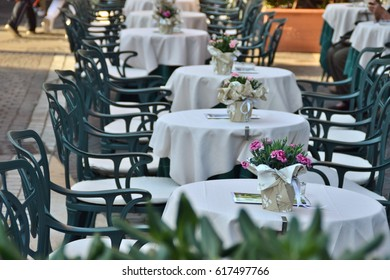 tables of a bar with flower pots