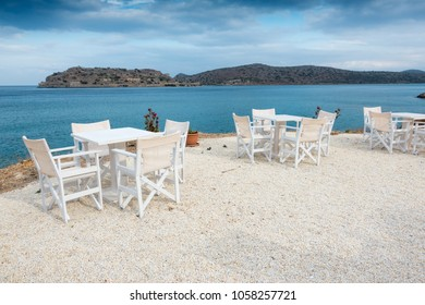 Tables and chairs arranged at outdoor sea facing restaurant
