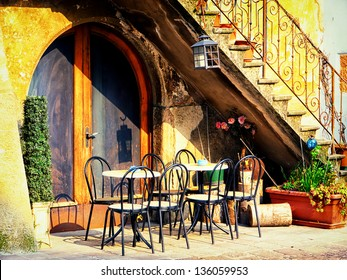 Tables And Chairs At A Bistro In Italy