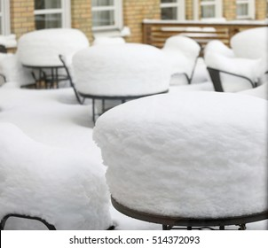 Tables and chairs covered with a thick layer of snow