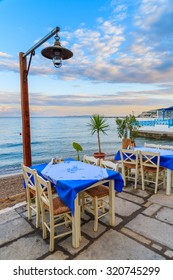 Tables with chairs in Greek restaurant on sea coast at sunset time, Samos island, Greece