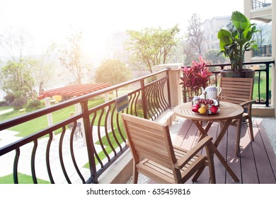 The tables and chairs on the balcony in the sunlight