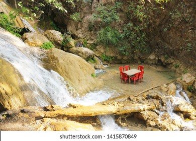 Tables and chairs of outdoor cafes in the waters of the waterfall. Romantic place in the Indian jungle. Waterfall in Rishikesh, India.