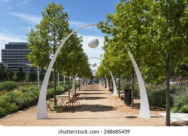 Tables and chairs sit inside the arches of a tree lined eating area in a public park