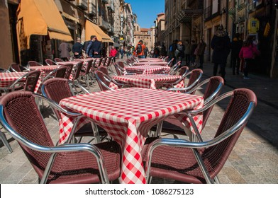 Tables and chairs situated outside of the bar on one of the main streets in the center of Salamanca, Spain,  on a sunny day in springtime